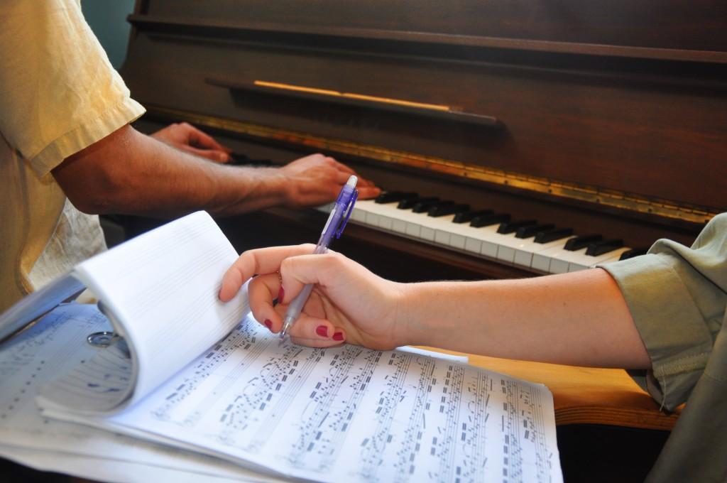 יד כותבת תווים ומאחורה ידיים מנגנות על פסנתר