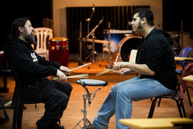 מורה מלמד תלמיד איך לנגן על תופים