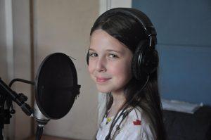 ילדה שרה באולפן הקלטות בקייטנות המוסיקה