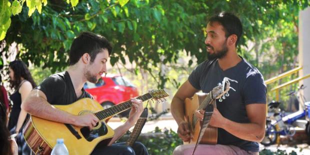2 אנשים מנגנים בגיטרה על הדשא ברימון