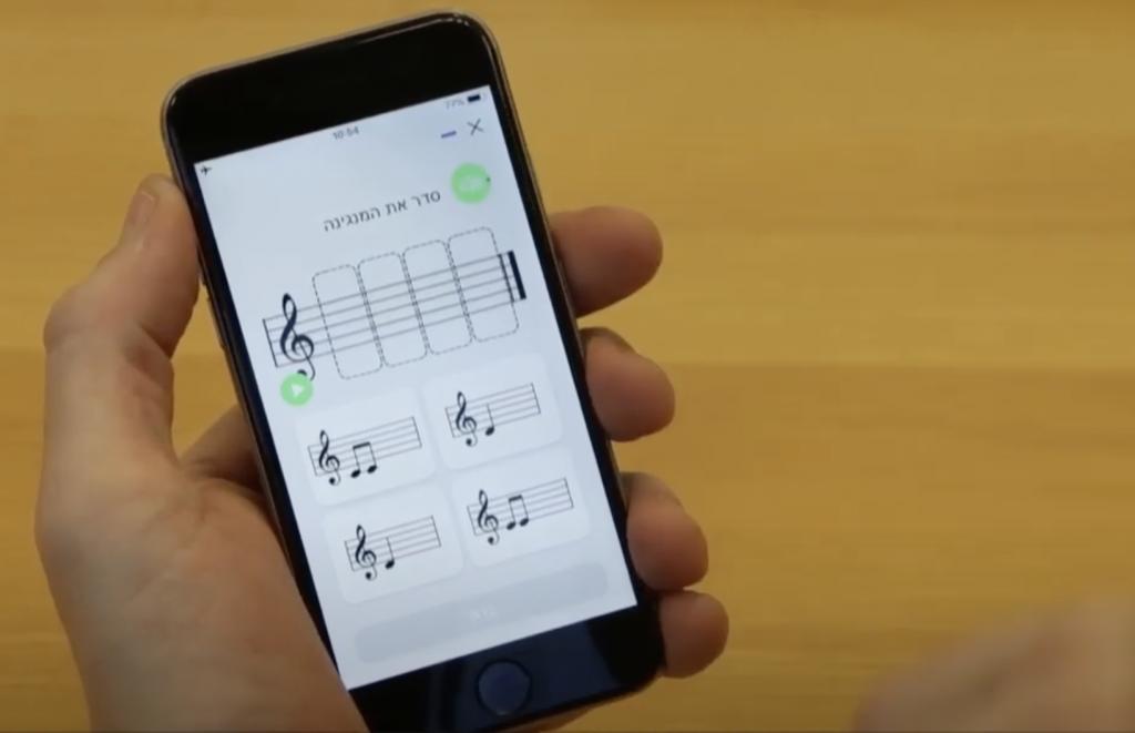 יד מחזיקה מכשיר סלולארי ובו אפליקציה מוסיקלית