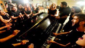 סטודנטים שרים סביב פסנתר במחזמר